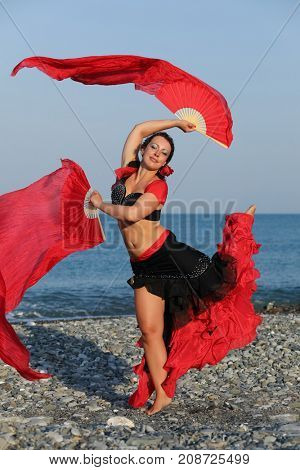 Dancer woman in black and red suit with fan dancing on seashore, stands on one leg