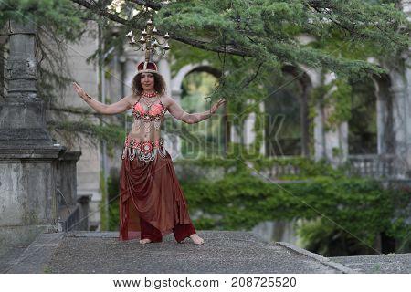dancer dancing belly dance with chandelier on head on background of building of Ordzhonikidze sanatorium
