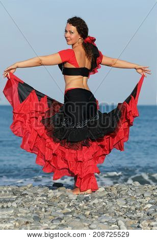 dancer woman in black and red suit dancing on seashore, straightened her skirt