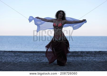 Dancer woman in black and red suit with handkerchief dancing on seashore, evening