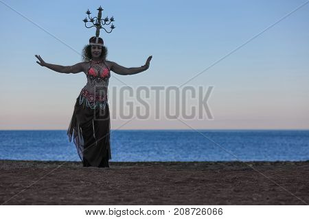 woman dancing belly dance with lit candelabrum on head, evening