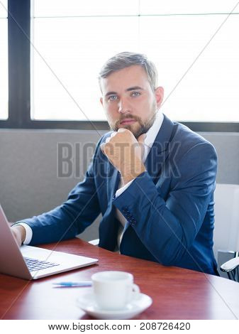 Businessman sitting, working behind laptop at office desk in office, looking serious in good blue suit