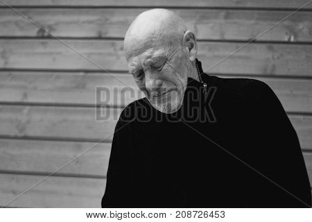 Black and white horizontal capture of handsome crying senior expressing pain of loss closing eyes from suffer. Old senior man closeup portrait. People feelings human concept.