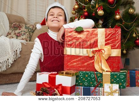 Boy near christmas tree and gift boxes, happy holiday and winter celebration, dressed in red