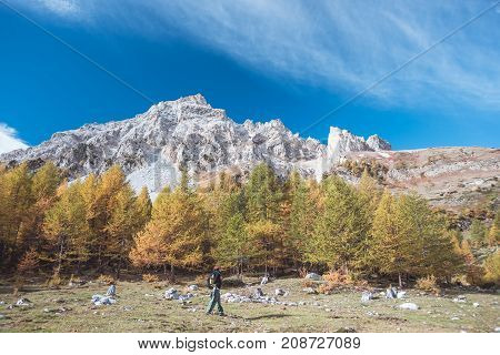 Hiker Walking On A Colorful Valley With Great Panoramic View And Autumnal Vivid Colors. Wide Angle S