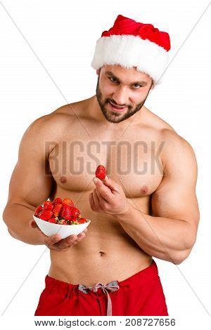 Portrait of a very muscular and passionate young man in a santa uniform, eating sweet strawberries isolated on a white background.