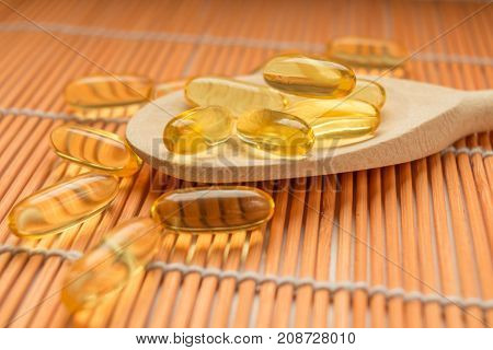 Fish liver oil omega 3 gel capsules on wooden spoon
