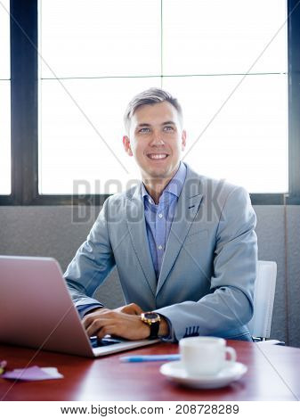 Businessman sitting, working behind laptop at work desk in office smiling with view in good gray suit