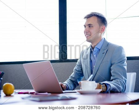 Businessman sitting, working behind laptop at work desk in office smiling with view in nice gray suit and large plan