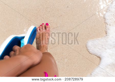 Woman Legs Stands In Sea Water On A Tropic Beach