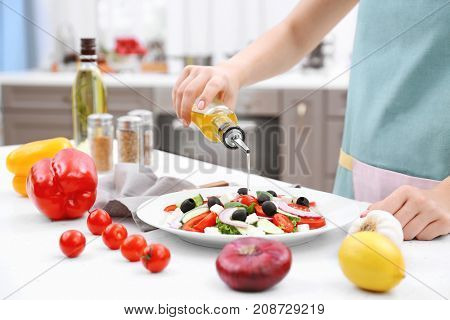 Woman pouring olive oil onto vegetable salad in kitchen