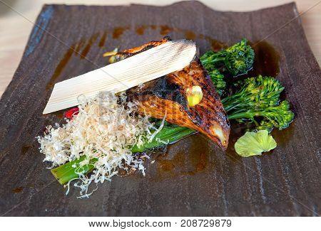 Japanese Grilled Miso Black Cod Fish with Broccoli Vegetable Bonito Flake on Stone Platter closeup macro