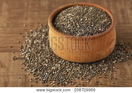 Bowl with chia seeds on wooden table