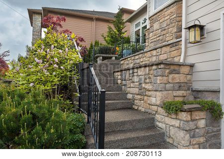 House frontyard cultured veneer stone work siding and rod iron stairs