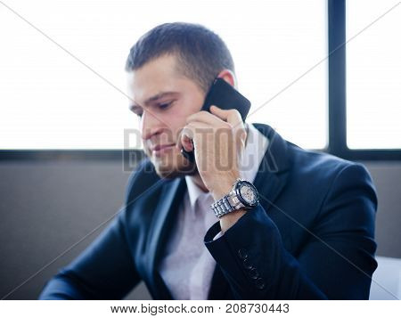 Successful bearded business man talking on a phone and working on a blurred office background. Young manager in a formalwear. Copy space.