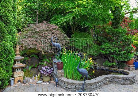 Home Garden Backyard with lush plants Japanese landscaping pond stone pagoda bronze cranes and paver brick patio