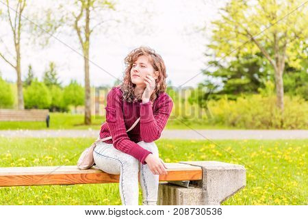 Young Woman With Hand On Face Sitting On Bench On Sidewalk In Green Downtown City Park In Saguenay,
