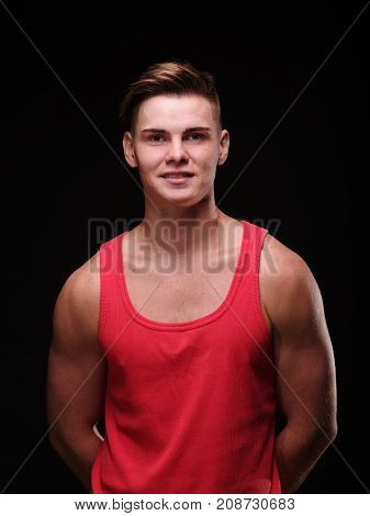 Portrait of a young man on a black background in a red tank top. He looks at the camera. Close-up.