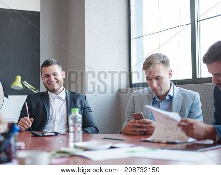 Two businessmen in expensive suits consider the papers work in a team to quickly solve problems against the background of a third businessman