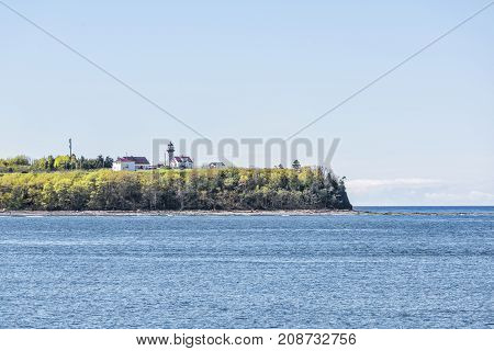 Peninsula Coast View Of Phare Du Cap De Madeleine Lighthouse And Red Painted Houses In Saint Lawrenc