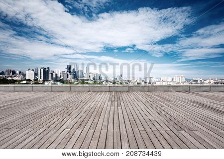 empty wooden floor and cityscape of kuala lumpur in cloud sky