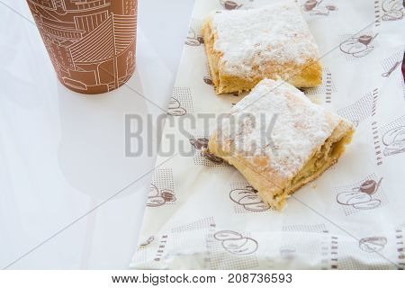 Two sweet strudel near the cardboard cup. Pastry plated by powdered sugar. Fast food.