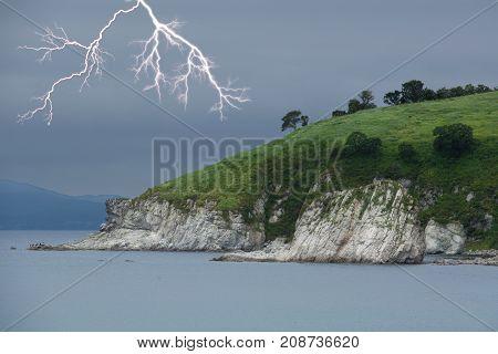 Lightning above green foreland. Seascape. Overcast sky.