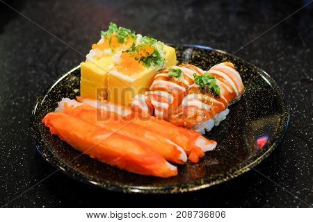 Grilled toro salmon sushi (sake nigiri) and mayonnaise top on rice Japanese rolled omelette (tamagoyaki) with shrimp eggs (tobiko) spring onion and imitation crab stick serve on black plate.
