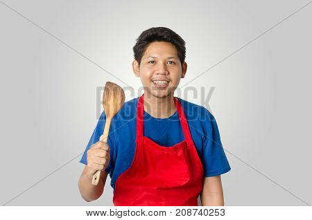 Asian man wear red apron and holding wooden ladle for cooking isolated on gray background