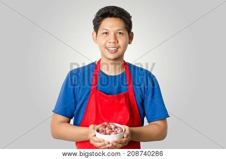 Asian man wear red apron and holding shallot in a bowl for cooking isolated on gray background