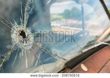 The windshield of a junkyard vehicle is cracked and splintered from what appears to be a bullet hole