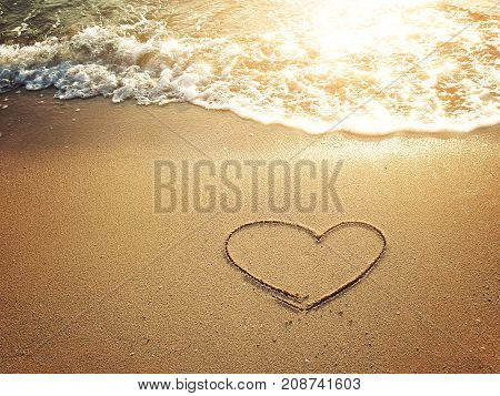 Hearts drawn on the sand of a beach with white bubble waves at sunset time
