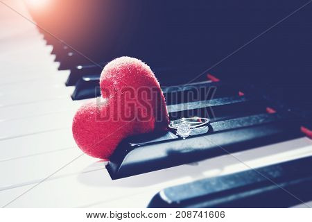 Ring and a hearts on piano vintage tone. Valentines Day background wedding day. Love concept