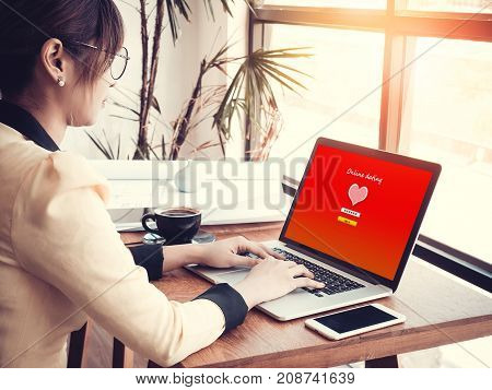 online love concept: office girl using online dating website on a laptop display hardwood desktop and stationery on background