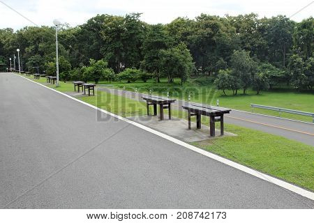 Empty wooden benches on the side of the road to see a beautiful views of garden with big trees. Transit stops and views of Chiang Mai University Thailand.