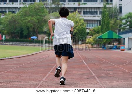 Runner athlete man running on the trackrace . Jogging for healthy concept