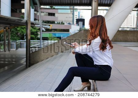 Side view of lonely Asian woman sitting on stairway and holding mobile smart phone in her hands.