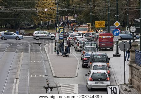 Car traffic and tram station in Lubicz street Cracow Poland - October 13 2017: People are waiting for tram cars are in traffic jam because of road works Lubicz street Cracow Poland.