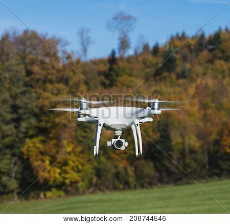 Ringlikon, Switzerland - 13 October, 2017: a DJI Phantom 4 Pro drone flying over a field, colorful trees in the background, selective focus on the front of the drone. Phantom 4 Pro drone is designed and manufactured by the DJI company.