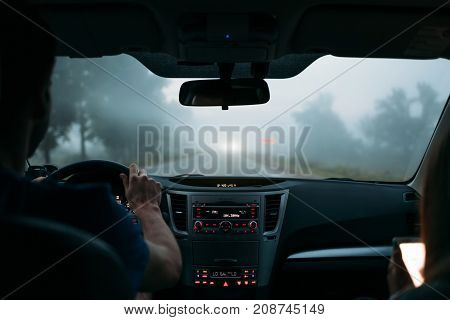 A Traveler Couple In The Car On The Way Home In Fog. Back View