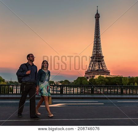 Young couple walking in Paris close to Eiffel Tower in the evening.