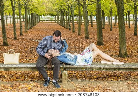 Romantic couple relaxing together on a stone bench in a park in autumn.