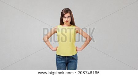 Dissatisfied wicked girl on a gray background. Human emotions.