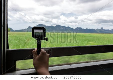 Action camera taking a picture of nature landscape through windows of the train.