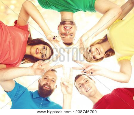 Smiling teenagers in colorful clothing standing together and making star with their fingers. Education, university, concept.