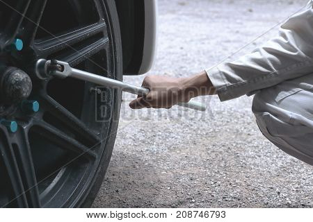 Close up hands of professional mechanic in white uniform holding wrench ready to changing tire of car at garage.