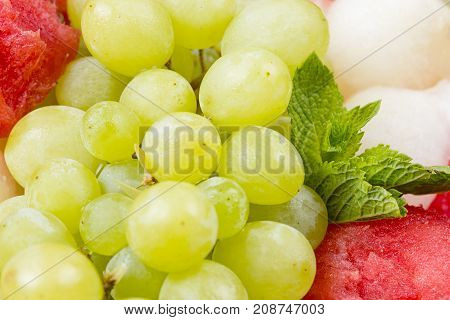 Photo of fruit platter - grapes and mint on white background