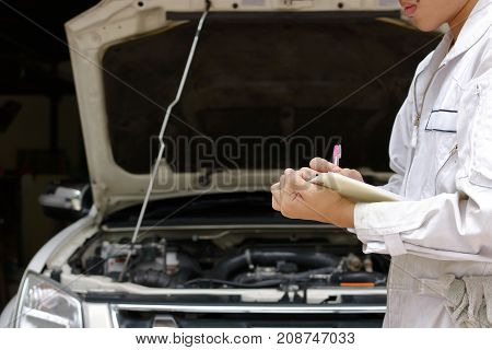Young auto mechanic in uniform writing on clipboard against car in open hood at the repair garage. Maintenance service concept.