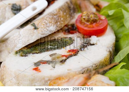 Stuffed seabass with salad and vegetables on plate