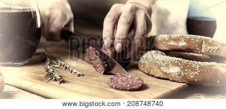 Close Up Of A Person's Hand Cut Salami On A Kitchen Board. Movie Effect